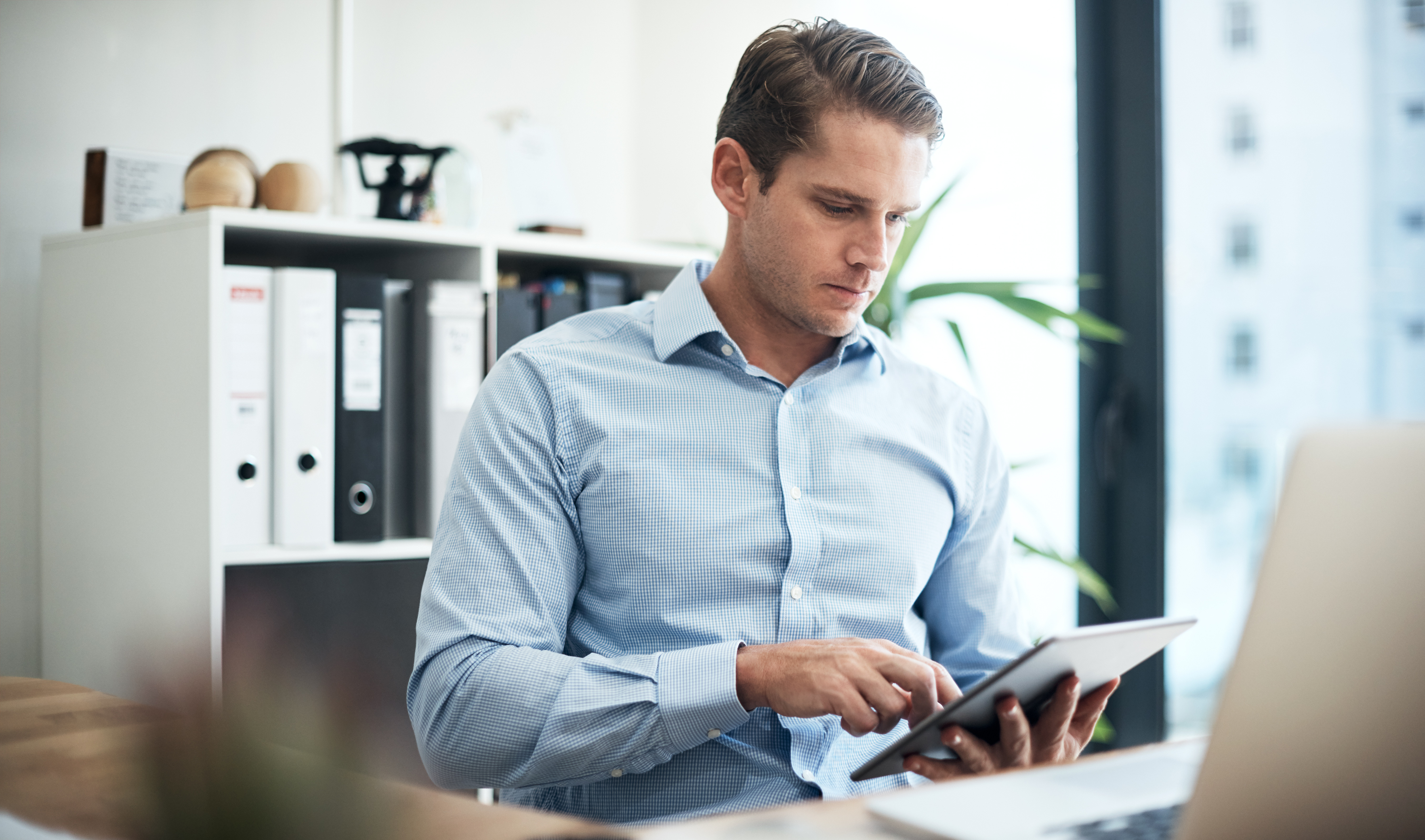 Young business man filling out survey on tablet